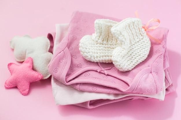 Roupas, meias e brinquedos para uma menina recém-nascida em uma mesa rosa