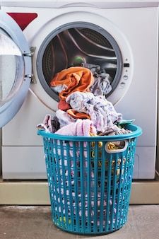 Roupas na cesta em frente à máquina de lavar.