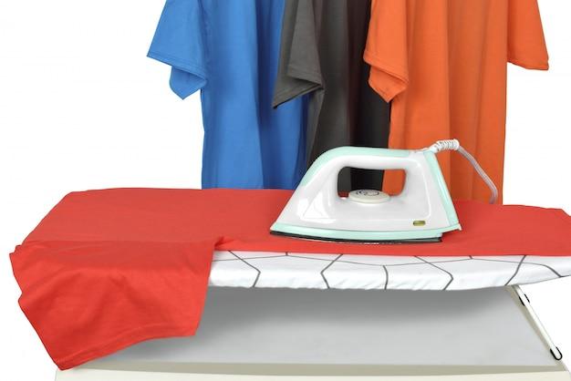 Roupas na tábua de passar roupa com ferro elétrico