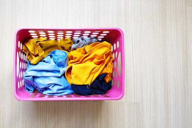 Roupas no cesto de roupa suja de plástico rosa. conceito de lavanderia