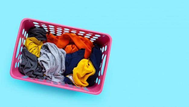 Roupas no cesto de roupa suja de plástico rosa sobre fundo azul.