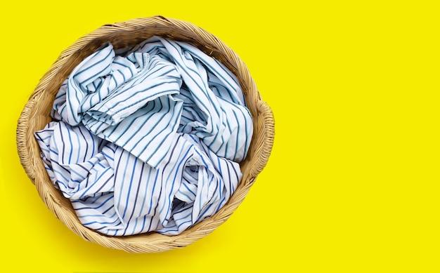 Roupas no cesto de roupa suja em fundo amarelo. copie o espaço