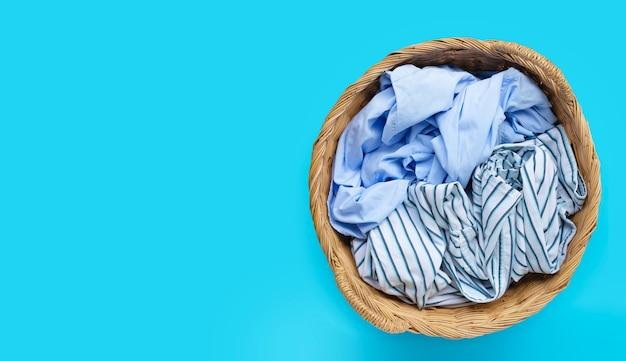 Roupas no cesto de roupa suja em fundo azul. copie o espaço