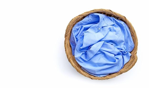 Roupas no cesto de roupa suja em fundo branco. copie o espaço