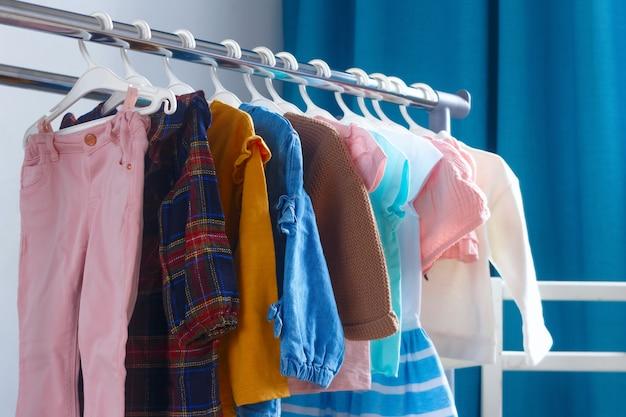 Roupas para menininhas penduradas no quarto das crianças