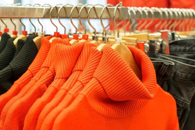 Roupas penduradas em cabides na loja, escolha do conceito de roupas