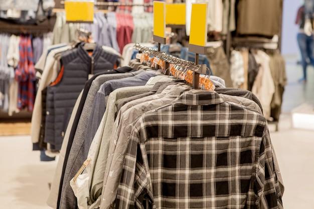 Roupas penduradas em uma prateleira. cabides de pano com camisas. roupas elegantes masculinas. conceito de moda e comércio
