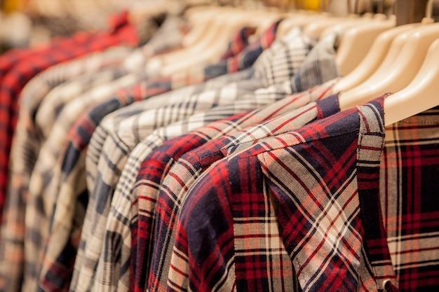 Roupas penduradas em uma prateleira. cabides de pano com camisas. roupas elegantes masculinas