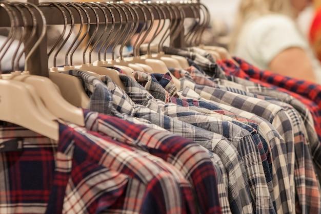 Roupas penduradas em uma prateleira. cabides de pano com camisas. roupas elegantes masculinas.