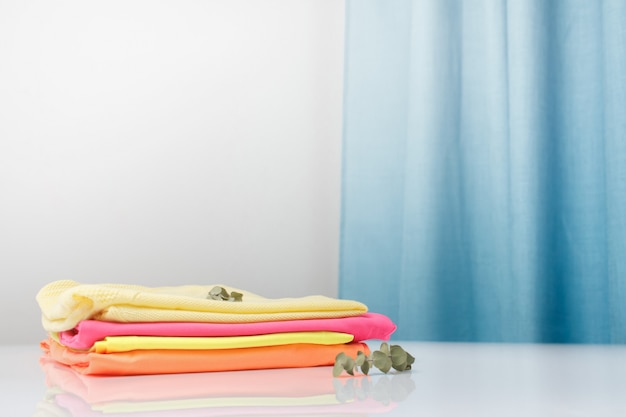 Roupas perfumadas de cores vivas são empilhadas.