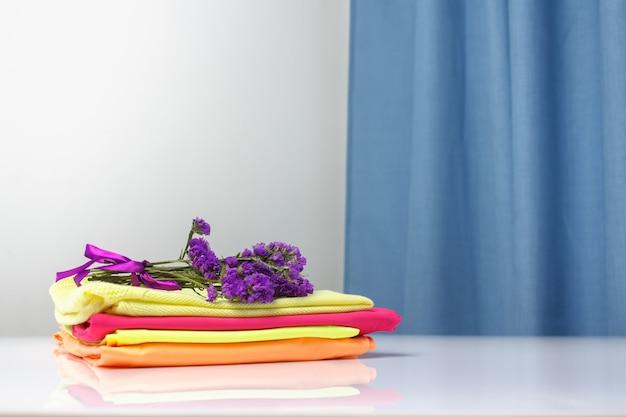 Roupas puras e perfumadas de cores brilhantes são empilhadas