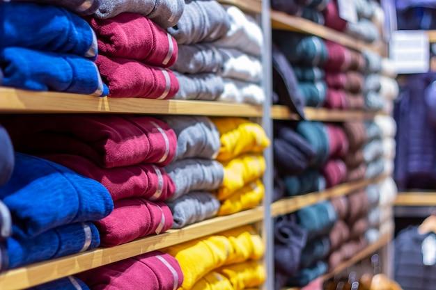 Roupas quentes dobradas ordenadamente em uma prateleira. uma linha de camisolas coloridas, casacos de malha, camisolas, camisolas, moletons com capuz no showroom ou loja.