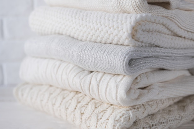 Roupas quentes e aconchegantes em cores claras com diferentes padrões de tricô closeup