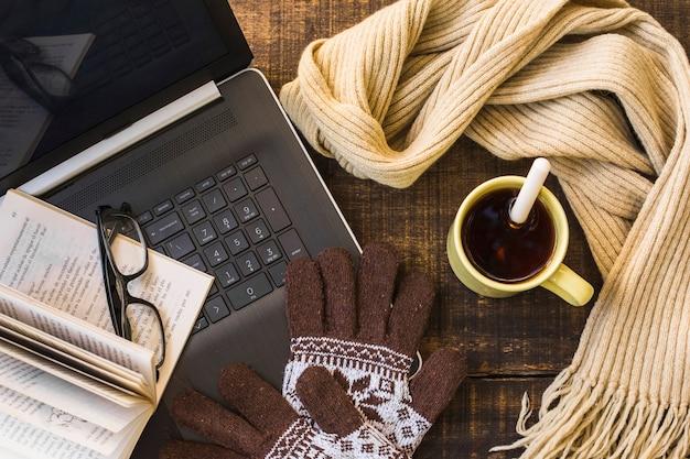 Roupas quentes e bebida quente perto de laptop e livro