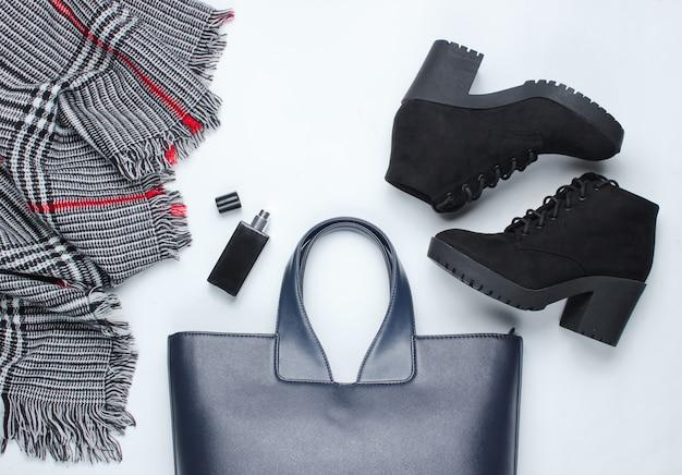 Roupas, sapatos e acessórios femininos em uma superfície branca