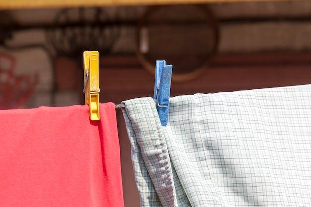 Roupas velhas lavadas e penduradas em uma corda em prendedores de roupa, vida rural na europa oriental