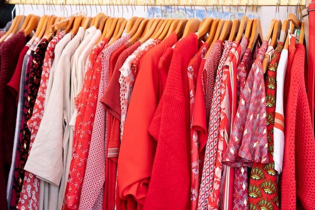 Roupas vermelhas em espera para venda na loja multicolorido em cabide para o verão