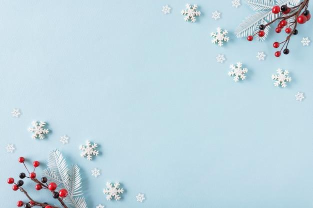 Rowan e flocos de neve em fundo azul pastel. conceito de inverno. camada plana, vista superior, espaço de cópia