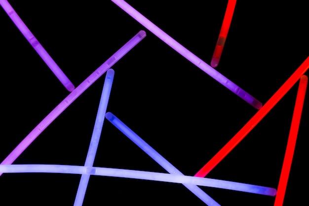 Roxa; palhas de néon azul e vermelho sobre fundo escuro