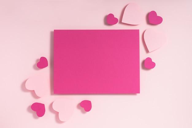 Roxo e rosa corações folha de papel em branco sobre fundo rosa pastel