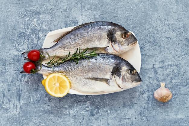 Royal dorade fresco com limão e tomate sobre fundo azul. conceito de comida saudável. vista superior, copie o espaço. conceito de frutos do mar do mediterrâneo.