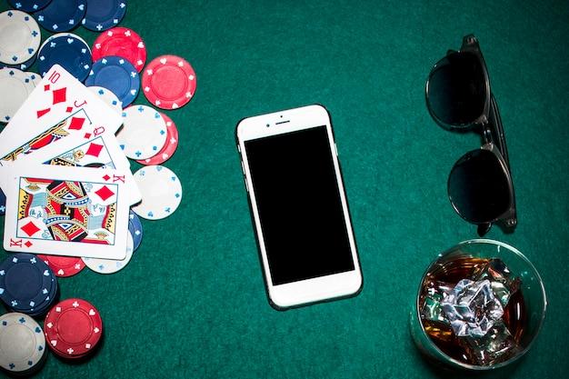 Royal flush baralho; fichas de casino; celular; óculos de sol e copo de uísque sobre o fundo de poker