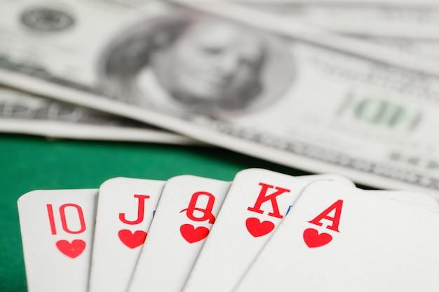 Royal flush de cartas de copas durante poker com dólares na mesa verde.