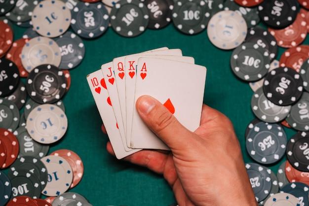 Royal flush no jogo de poker nas mãos do jogador no fundo de uma mesa verde com fichas de jogos