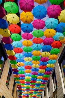 Rua artística decorada com guarda-chuvas coloridas