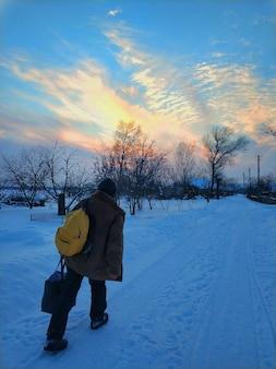 Rua coberta de neve na aldeia. um homem desce a rua.