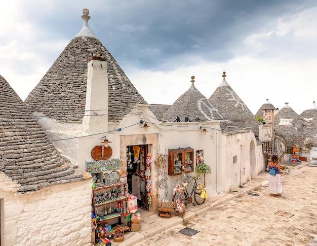 Rua colorida da vila de alberobello. edifícios trulli brancos, apúlia, itália
