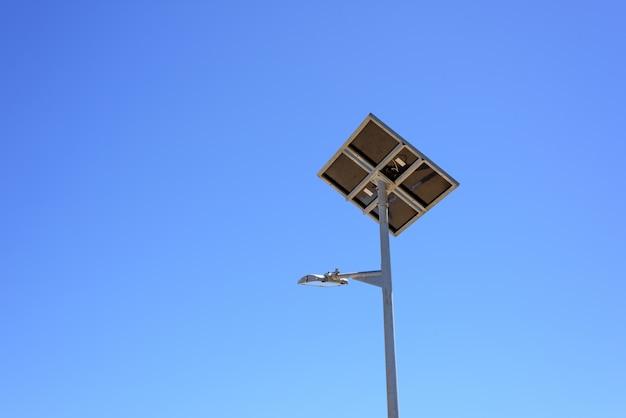 Rua com o painel solar no fundo do céu azul. energia verde.