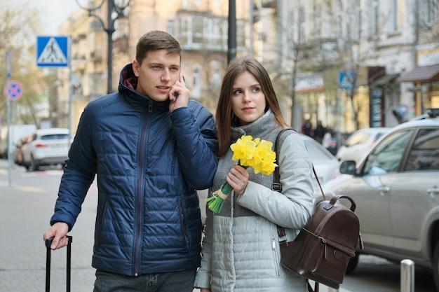 Rua da cidade de primavera, casal de jovens turistas com mala