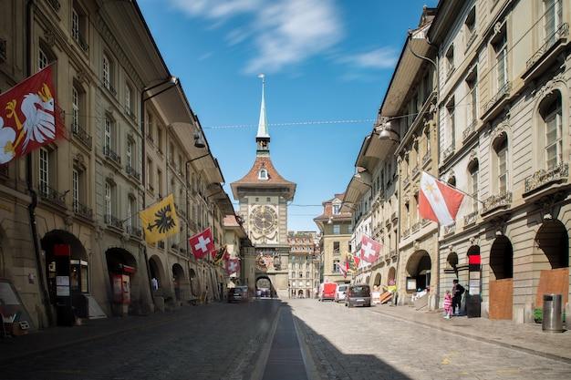Rua da compra com torre de pulso de disparo zytgloggein a cidade medieval velha de berna, suíça.