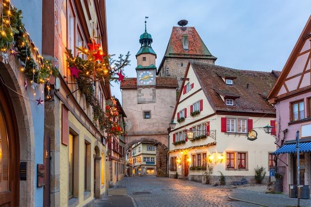 Rua de natal decorada e iluminada com portão e torre markusturm na cidade velha medieval de rothenburg ob der tauber, baviera, sul da alemanha
