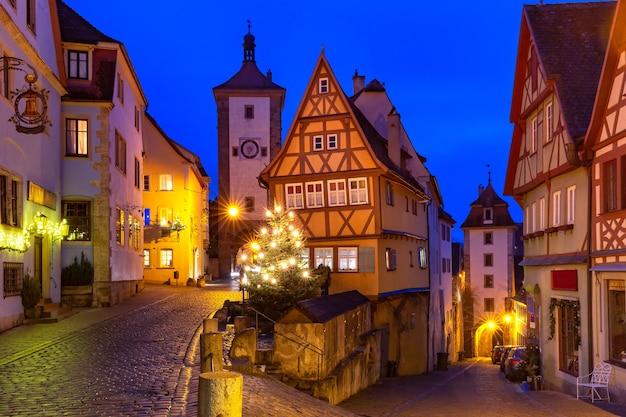 Rua de natal decorada e iluminada com portão e torre plonlein na cidade velha medieval de rothenburg ob der tauber, baviera, sul da alemanha