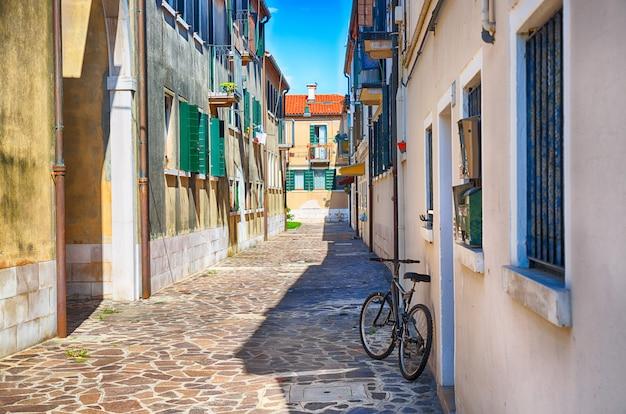 Rua estreita com uma bicicleta de manhã na ilha de murano, veneza, itália