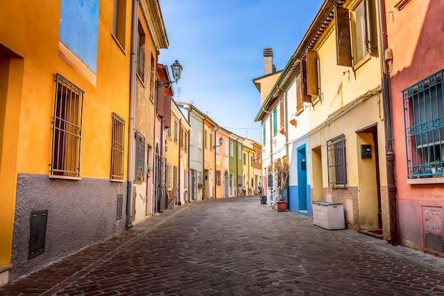 Rua estreita da vila dos pescadores san guiliano com casas coloridas e bicicletas no início da manhã em rimini, itália.