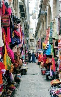 Rua estreita de mercado, com lojas e stan