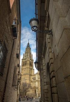 Rua estreita de toledo em que a torre da catedral de toledo é vista.