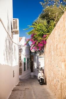 Rua estreita e aconchegante em lindos, ilha de rodes, grécia Foto Premium