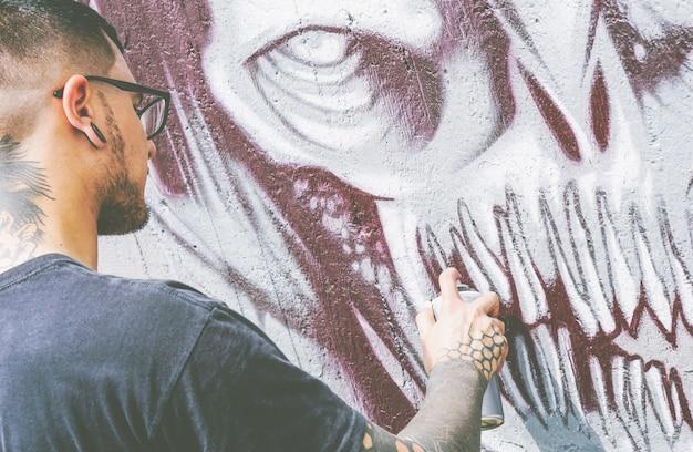 Rua grafiteiro pintando com um spray de cor um grafite de caveira monstro escuro na parede