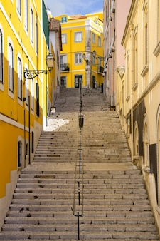 Rua íngreme típica com escadas longas e paredes coloridas da cidade de lisboa, portugal.