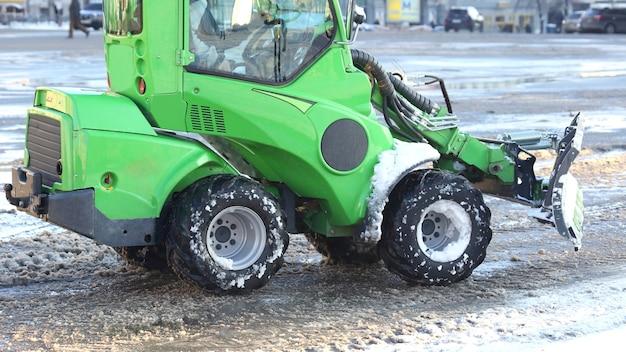 Rua limpando a cidade da neve com ajuda de mini equipamentos especiais