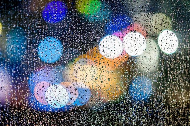 Rua luzes de bokeh com pingos de chuva no vidro da janela