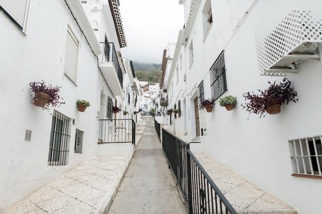 Rua pitoresca de mijas com vasos de flores nas fachadas. aldeia branca andaluza. costa del sol. sul da espanha.