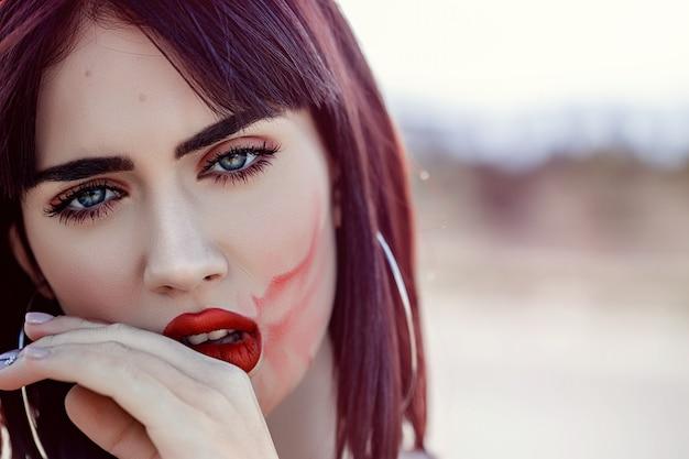 Rua retrato da bela jovem caucasiana menina de cabelos castanho com batom manchado no rosto
