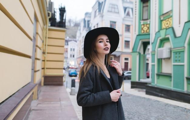 Rua retrato de uma mulher elegante andando pelas ruas da cidade velha e bonita.