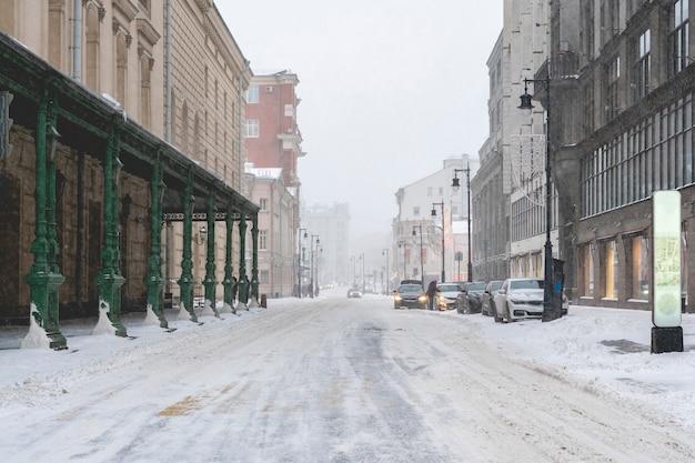 Rua secundária urbana. dia de nevoeiro. queda de neve na rua lateral deserta na cidade de inverno f