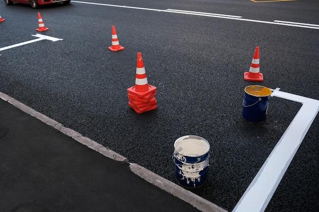 Rua sity novas marcações viárias no estacionamento de asfalto na faixa de rodagem ao longo da estrada processo de pintura